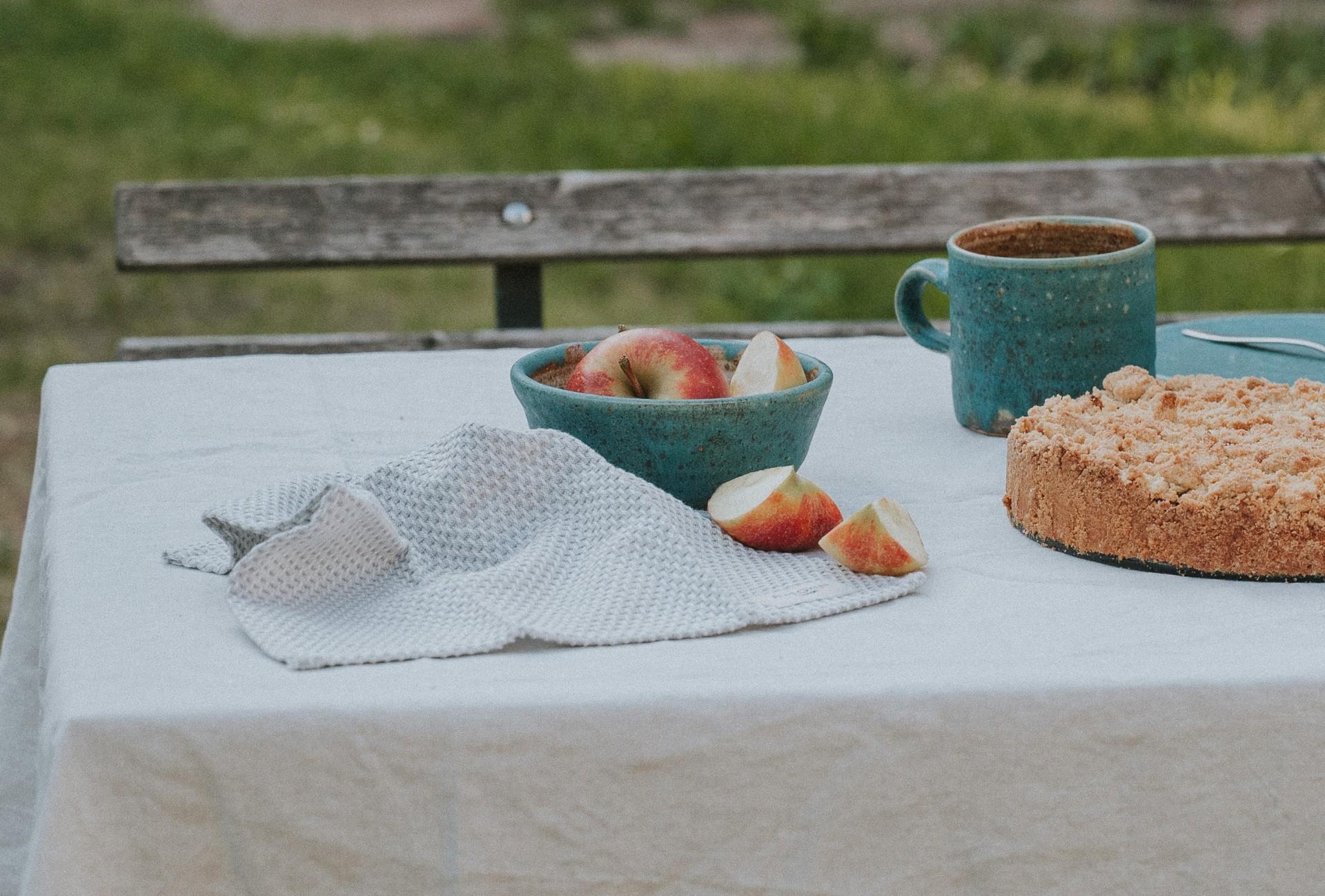 Ein Tisch im Garten mit Spültuch und Keramikschüssel