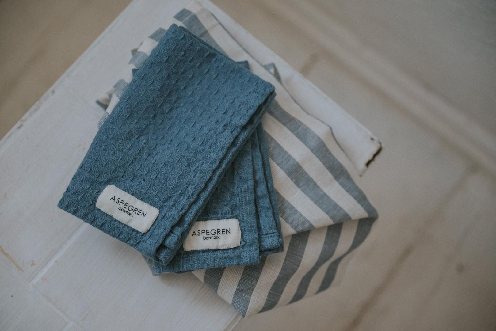 Geschirrtuch Bio-Baumwolle blau liegt auf einem kleinen weißen Hocker