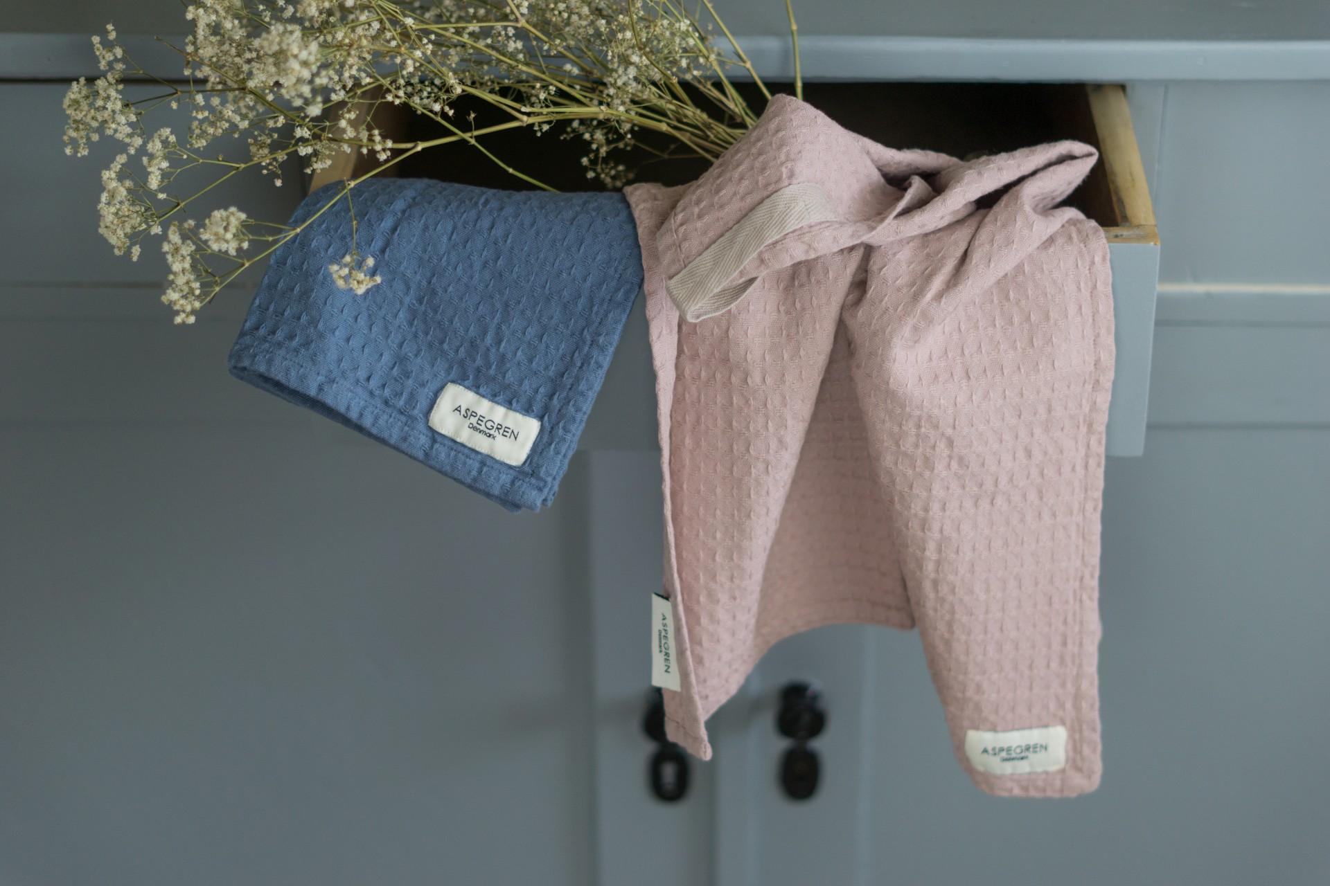 Geschirrtücher aus Bio-Baumwolle von Aspegren Denmark hängen aus einer offenen Schublade.